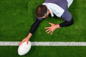 Rugby player scoring a try with one hand on the ball